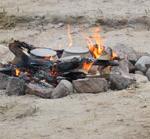 Kuvassa nuotio, jossa kaksi ruoka-astiaa kuumenemassa.